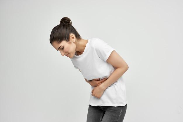 Женщина в белой футболке держит ее проблемы со здоровьем желудка диарея боль в животе