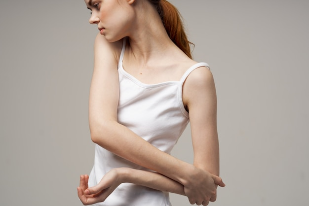 Женщина в белой футболке, держась за локоть, проблемы со здоровьем, лечение суставов в студии