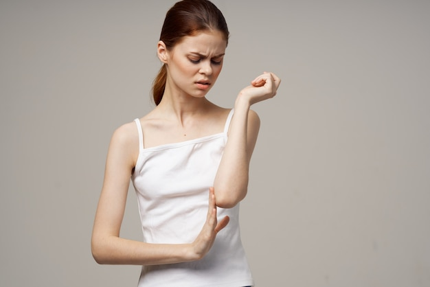 팔꿈치 건강 문제 공동 치료 스튜디오 치료를 들고 흰색 티셔츠를 입은 여성