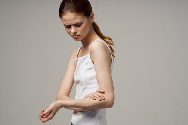 肘の健康問題関節治療スタジオ治療を保持している白いtシャツの女性