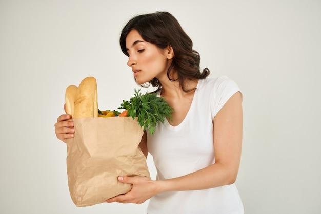 식료품 배달 밝은 배경이 있는 흰색 티셔츠 패키지를 입은 여성