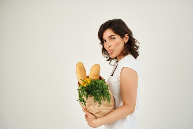 슈퍼마켓 음식 배달에서 식료품과 함께 흰색 티셔츠 패키지를 입은 여성