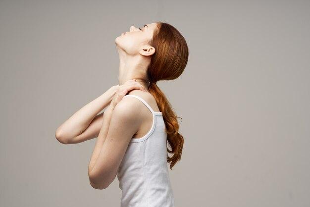 Женщина в белой футболке ревматизм боли в шее проблемы со здоровьем светлый фон