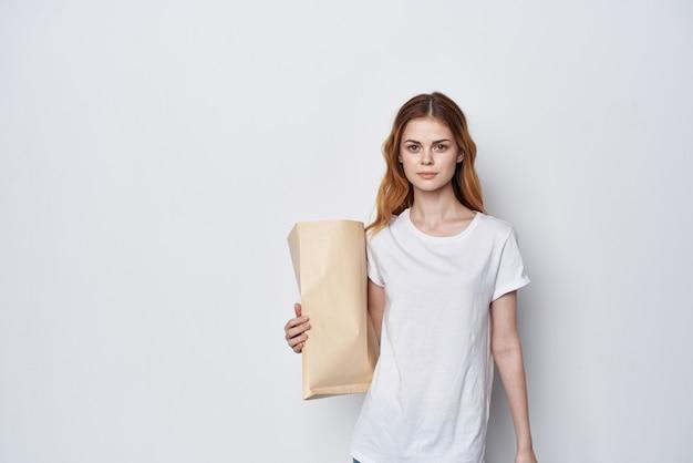 Женщина в белой футболке с пакетом продуктов, упаковка для покупок