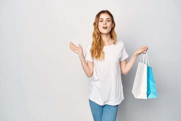 手のショッピングショップでパッケージと白いtシャツの女性