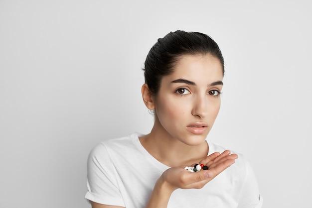 手の健康療法のライフスタイルの丸薬と白いtシャツの女性