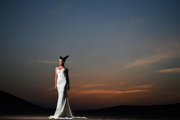 Женщина в белом свадебном платье на закате девушка в платье на открытом воздухе в вечернем небе невеста