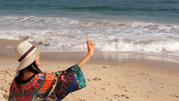 Женщина в шляпе с широкими полями любит делать селфи на волнистом пляже