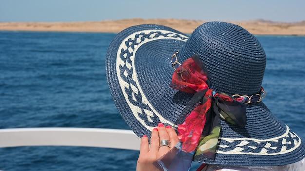 챙이 넓은 모자를 쓴 여성은 바다 여성을 배경으로 고급 쾌속정 갑판에 앉아 있다