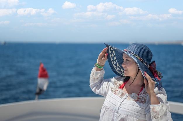 챙이 넓은 모자를 쓴 여성이 바다 배경의 고급 쾌속정 갑판에 앉아 있다