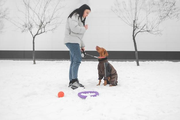 Женщина в зимней одежде и собака на поводке стоят в снегу