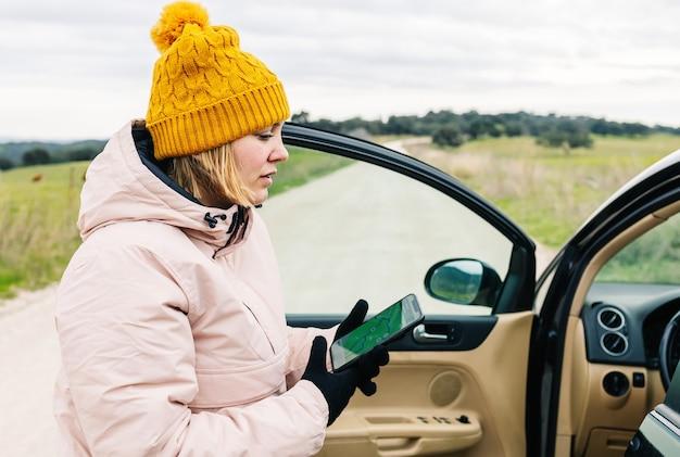 Женщина в зимней одежде выходит из машины и смотрит на цифровую карту на своем мобильном телефоне.