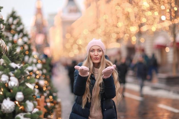 ピンクのセーターを着た冬の服を着た女性が正月に飾られた街を歩く