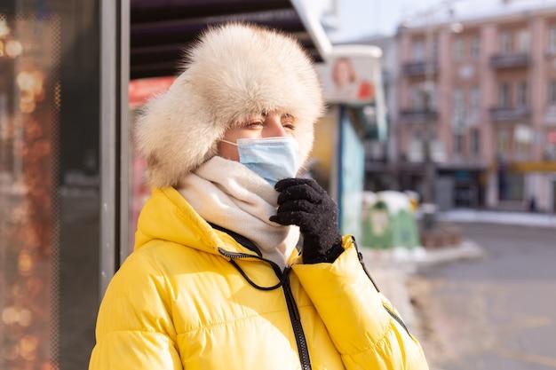 Женщина в зимней одежде в холодный день ждет автобуса на автобусной остановке