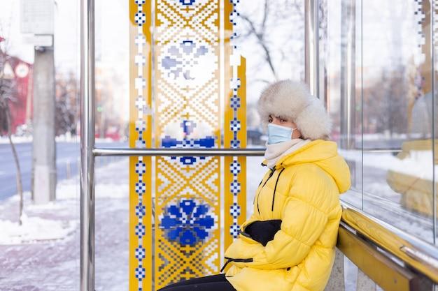 バス停でバスを待っている寒い日に冬服を着た女性