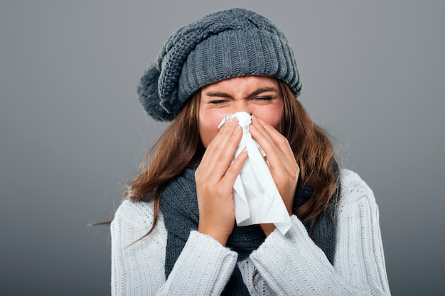 Женщина в зимней одежде чихает