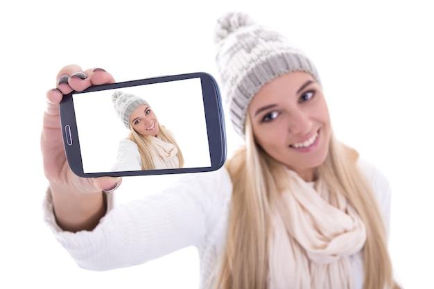 흰색으로 격리된 스마트폰으로 셀카 사진을 찍는 겨울 옷을 입은 여자