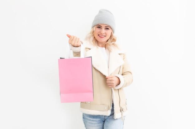 겨울 옷을 입고 선물, 선물, 쇼핑백을 들고 웃고 있는 여자