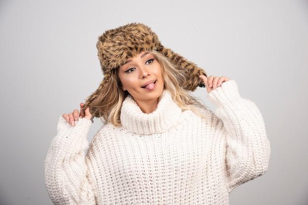 그녀의 혀를 튀어 나와 겨울 모자에있는 여자.