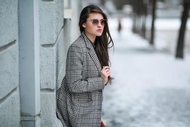 おしゃれなコートを着て通りを歩いて寒い冬の女性