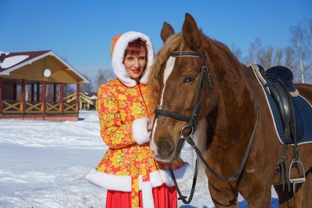 馬とポーズをとって冬の女性