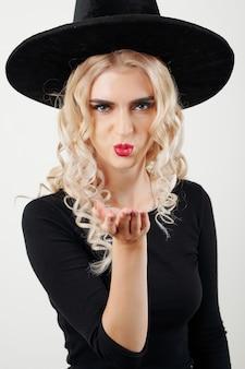 Женщина в костюме ведьмы посылает воздушный поцелуй