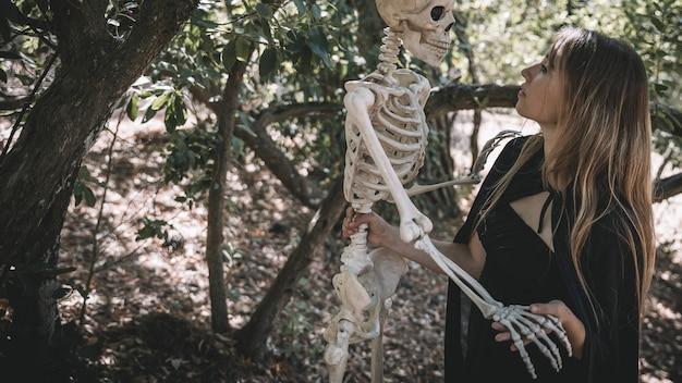 Женщина в костюме ведьмы, держащая над головой скелет