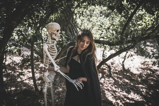 Женщина в костюме ведьмы, держащей скелет и глядя вниз