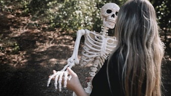 Woman in witch costume leaning skeleton