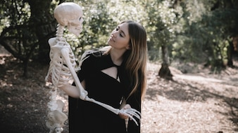 Woman in witch suit looking at skeleton