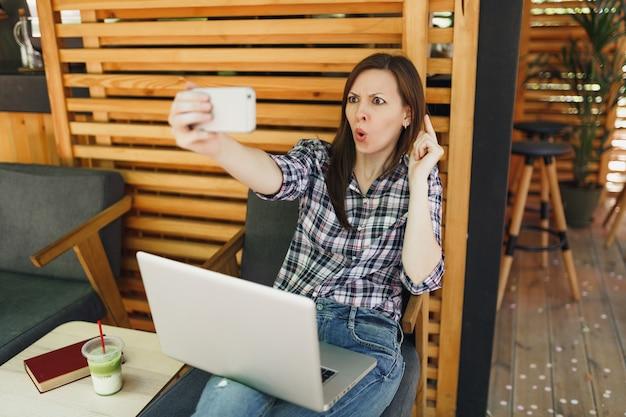 ノートパソコンのパソコンと一緒に座って、携帯電話で自分撮りをして、自由時間にリラックスして、木製の屋外通りの夏のコーヒーショップの女性。モバイルオフィス