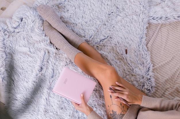 여자 양모 양말과 스웨터 핑크 노트북 기호 2021, 엉덩이에 큰 문신. 여성은 침실에서 집에서 침대에 앉아있다.