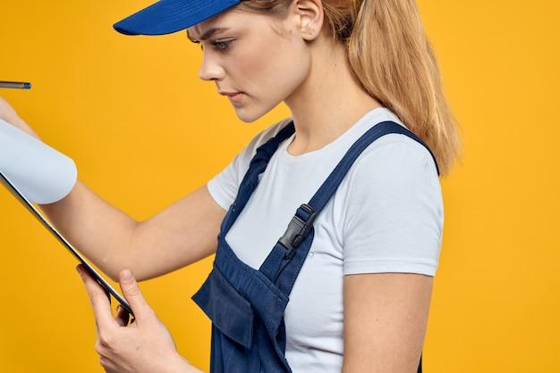 Женщина в форме работы документов курьерской службы желтом фоне. фото высокого качества