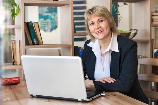 Женщина работает на ноутбуке в офисе. женщина средних лет улыбается в кафе.