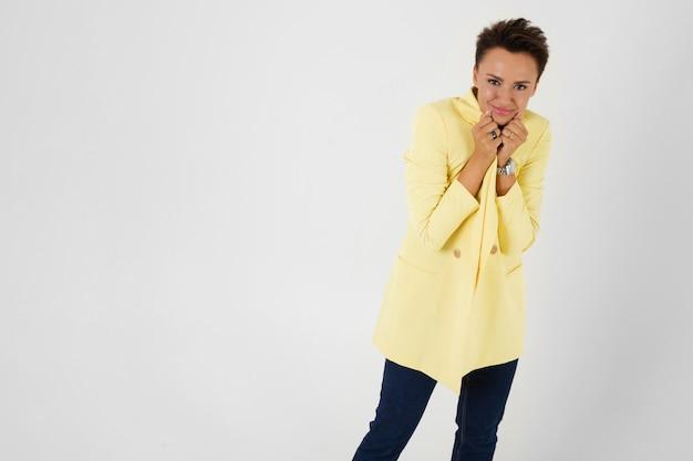 Женщина в желтом осеннем пальто холодная