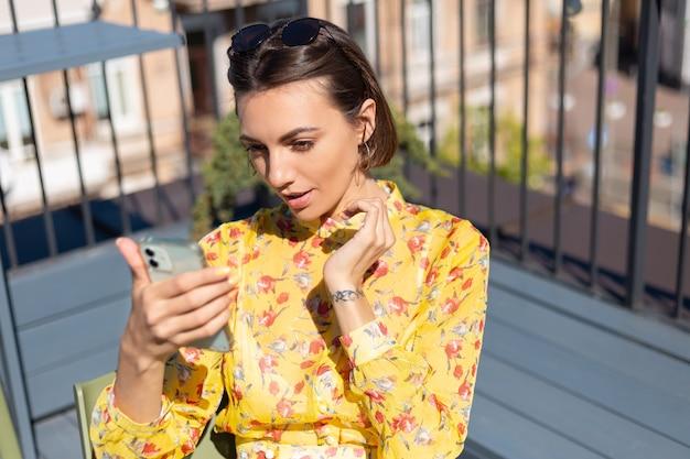 화창한 날에 휴대 전화로 여름 카페에서 테라스에 노란색 드레스를 입은 여자가 셀카를 받아 화상 통화를합니다.