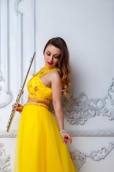 明るい質感の背景にフルートと黄色のドレスの女性
