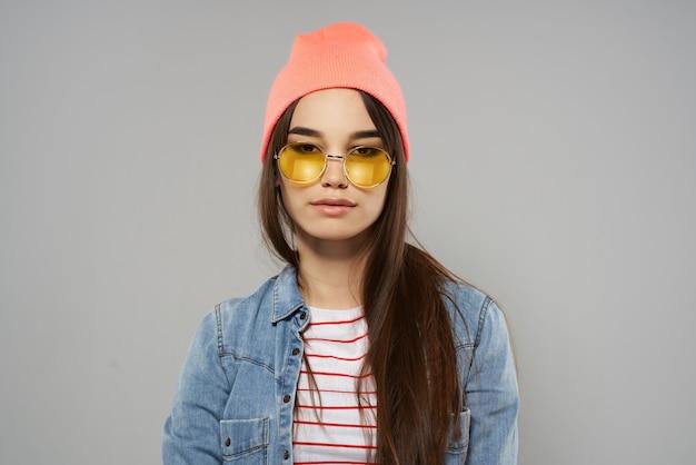 モダンなスタイルの灰色の背景に黄色いメガネピンクの帽子ファッションの女性