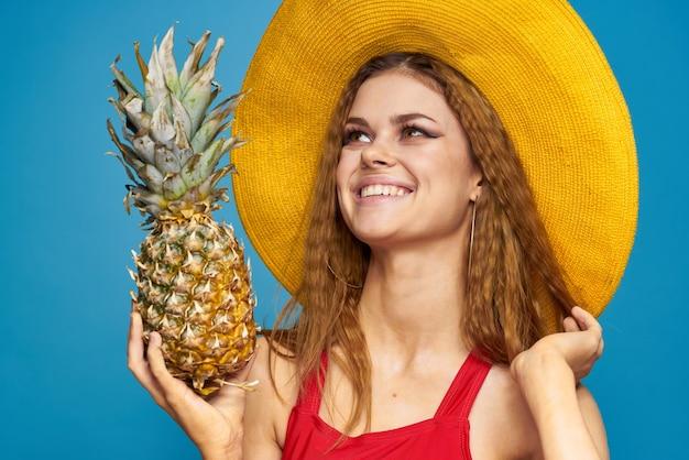 手にパイナップルと黄色い帽子の女性感情楽しいライフスタイル夏フルーツ青い背景。高品質の写真