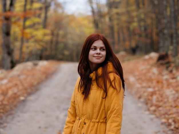 秋の森の散歩でイエロージャケットの女性