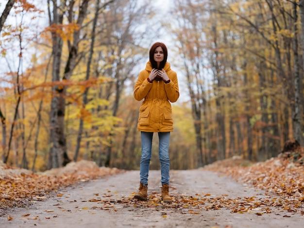 森の道の旅紅葉の黄色いジャケットの女性