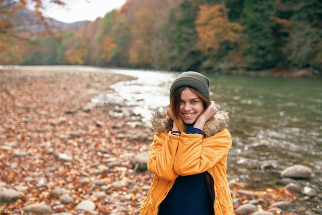 自然旅行川秋にイエロージャケットの女性