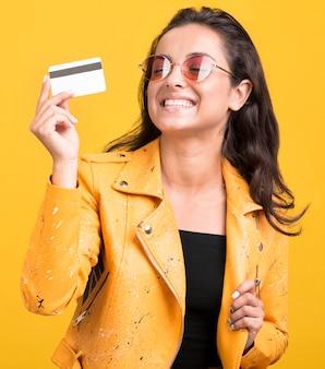 그녀의 카드 중간 샷을 보여주는 노란색 재킷을 입은 여자
