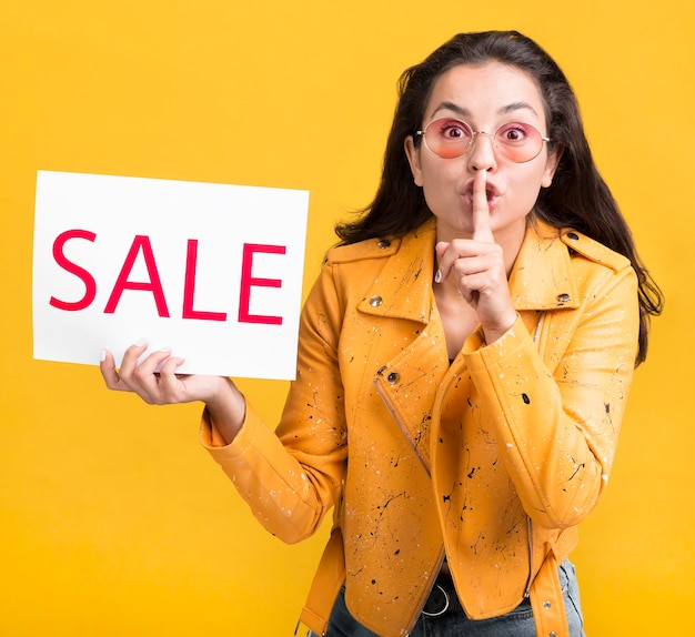 Женщина в желтой куртке, молчаливый жест продаж