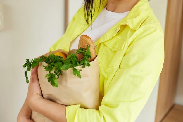 Женщина в желтой куртке стоит с бумажным пакетом для покупок, полным свежих фруктов и овощей дома