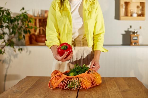 노란색 재킷에 여자는 부엌에 건강한 야채와 과일 쇼핑 메쉬 에코 가방을 풀고
