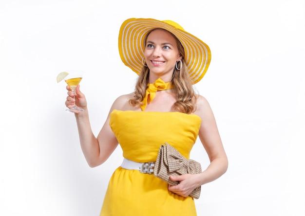 黄色の枕ドレス、財布と白い背景のカクテルグラス笑顔と帽子の女性。夏のコンセプトです。家の隔離を維持するための枕の挑戦。