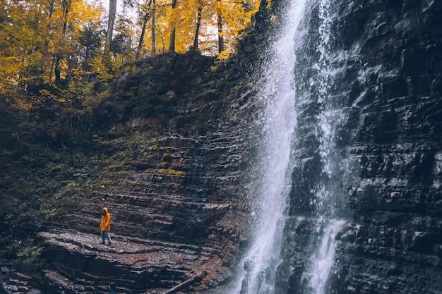 秋の滝のハイキングの概念で黄色のレインコートの女性