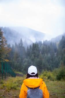 秋の山のコピースペースで黄色のレインコートハイカーの女性