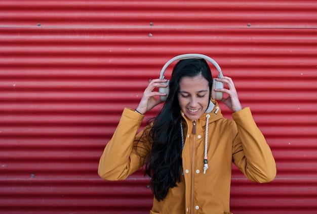 빨간 벽에 기대어 음악을 듣고 노란 우비에 여자